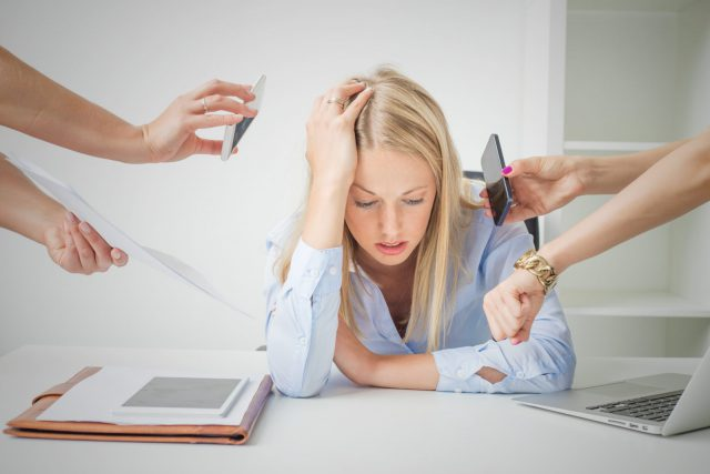 Work issues: woman overloaded with stuff at work
