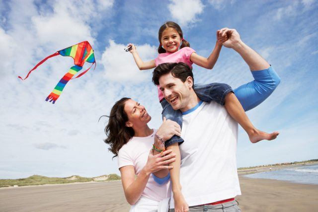 Family Having Fun Flying Kite On Beach Holiday Smiling And Laughing